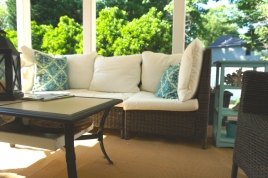 A large, weather-proof outdoor sofa invites others to share in the cool escape that the covered porch offers.
